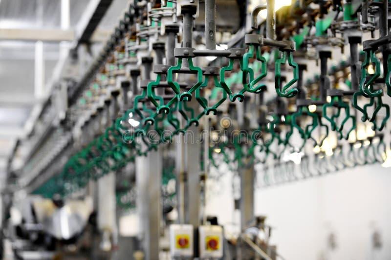 Ganchos vazios em uma fábrica de processamento da carne imagem de stock