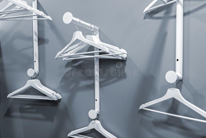 Ganchos vazios que penduram em uma cremalheira da roupa imagem de stock