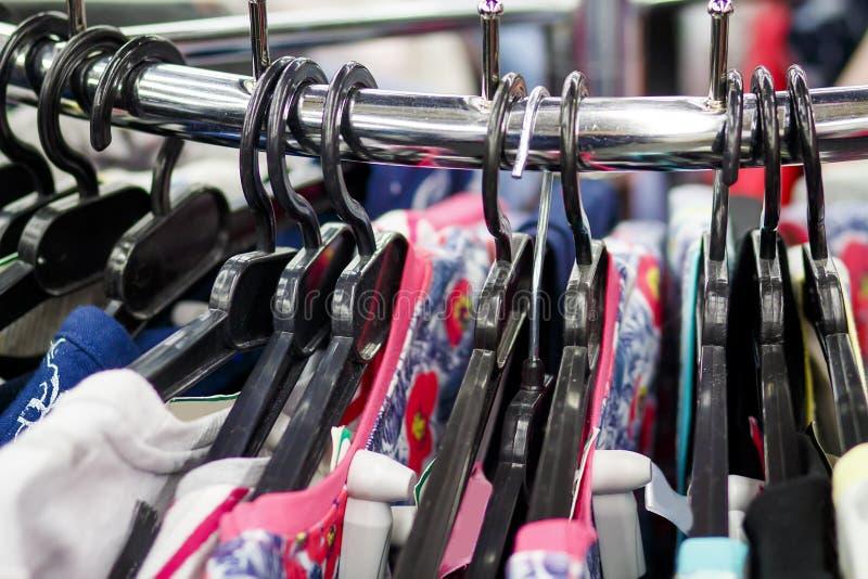 Ganci con i vestiti in un primo piano del boutique dell'abbigliamento alla moda Concetto dell'abbigliamento di acquisto Cose sui  immagine stock