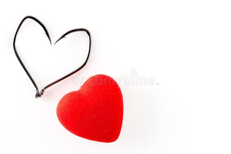 Ganci di pesca sotto forma di cuore e di cuore rosso su un fondo bianco immagini stock