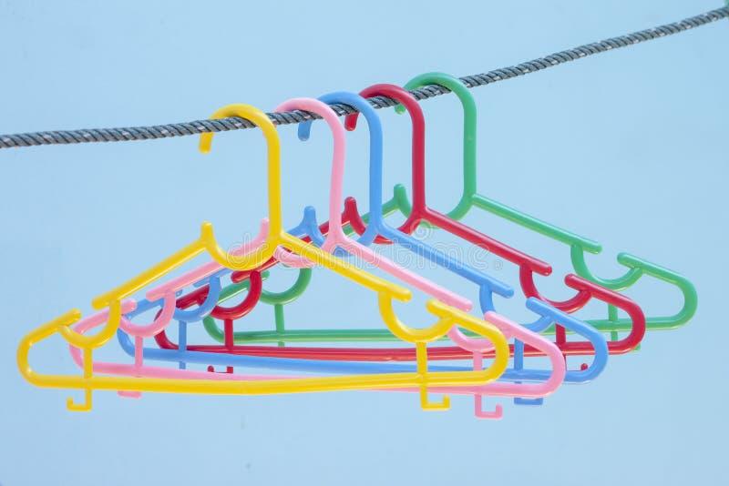Ganci di plastica variopinti sulla corda sul fondo della sfuocatura della parete fotografie stock libere da diritti