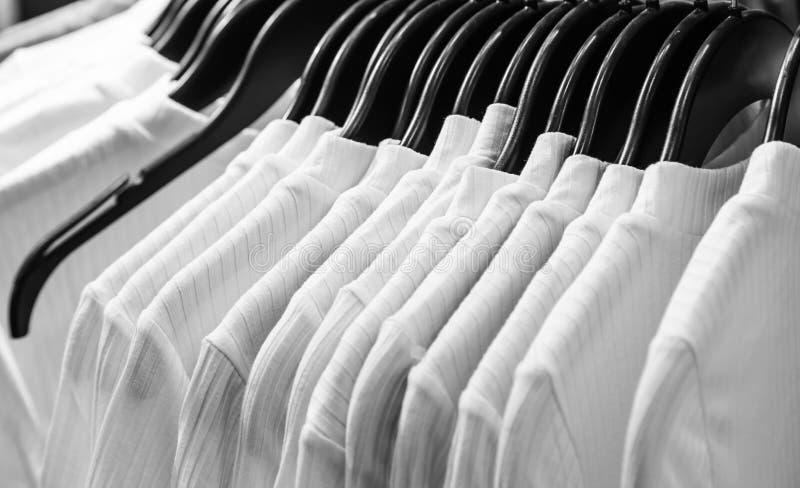 Ganci nel fondo di esposizione bianco del panno della maglietta fotografie stock libere da diritti