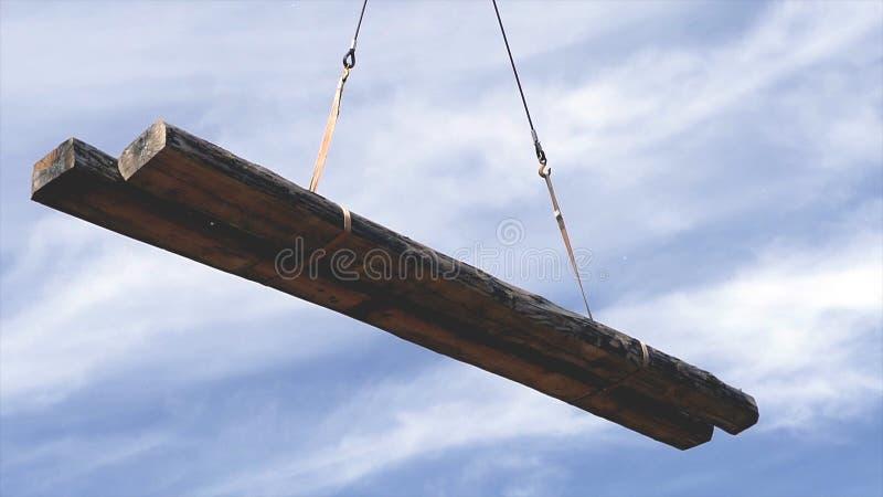 Gancio della gru che tiene legno clip La gru solleva un fascio su un cantiere Lavoro sul cantiere immagine stock libera da diritti