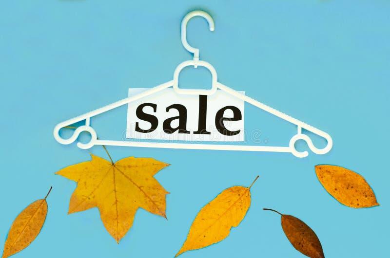 Gancio, foglie di autunno e asciutte e ` di vendita del ` di parola su fondo blu immagine stock libera da diritti