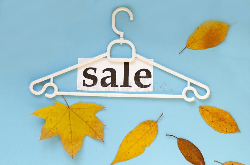 Gancio, foglie di autunno e asciutte e ` di vendita del ` di parola su fondo blu fotografia stock