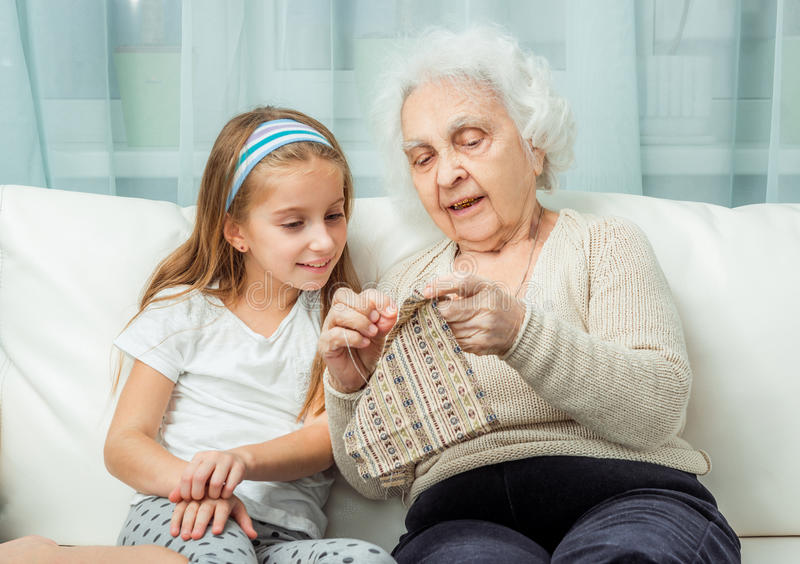 Ganddaughter learning to embroider with granny. On sofa stock photography