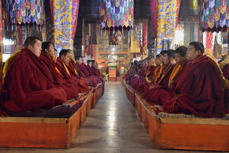 GANDEN, АВТОНОМНАЯ ОБЛАСТЬ ТИБЕТА - ОКОЛО МАЙ 2018: Тибетские монахи практикуя раздумье внутри монастыря Ganden стоковые изображения