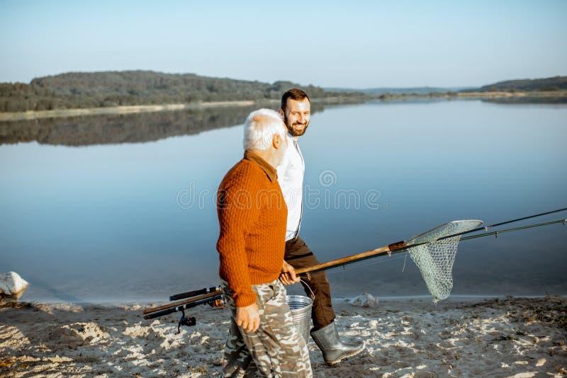 Gandfather mit dem erwachsenen Sohn, der für die Fischerei geht lizenzfreie stockbilder