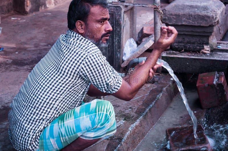 Gandhinagar, Gujrat, ?ndia maio de 2018 - foto do close up das m?os de lavagem do homem com ?gua da tubula??o perto da estrada da fotos de stock royalty free