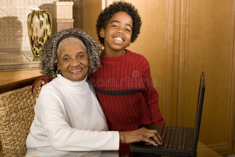 Gandmother en kleinzoon het typen op laptop in haar huis stock afbeeldingen