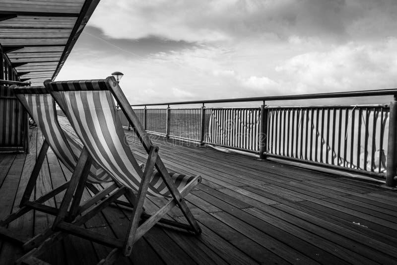 Gandulear sillas en el embarcadero de Boscombe, Bournemouth, Inglaterra imagen de archivo