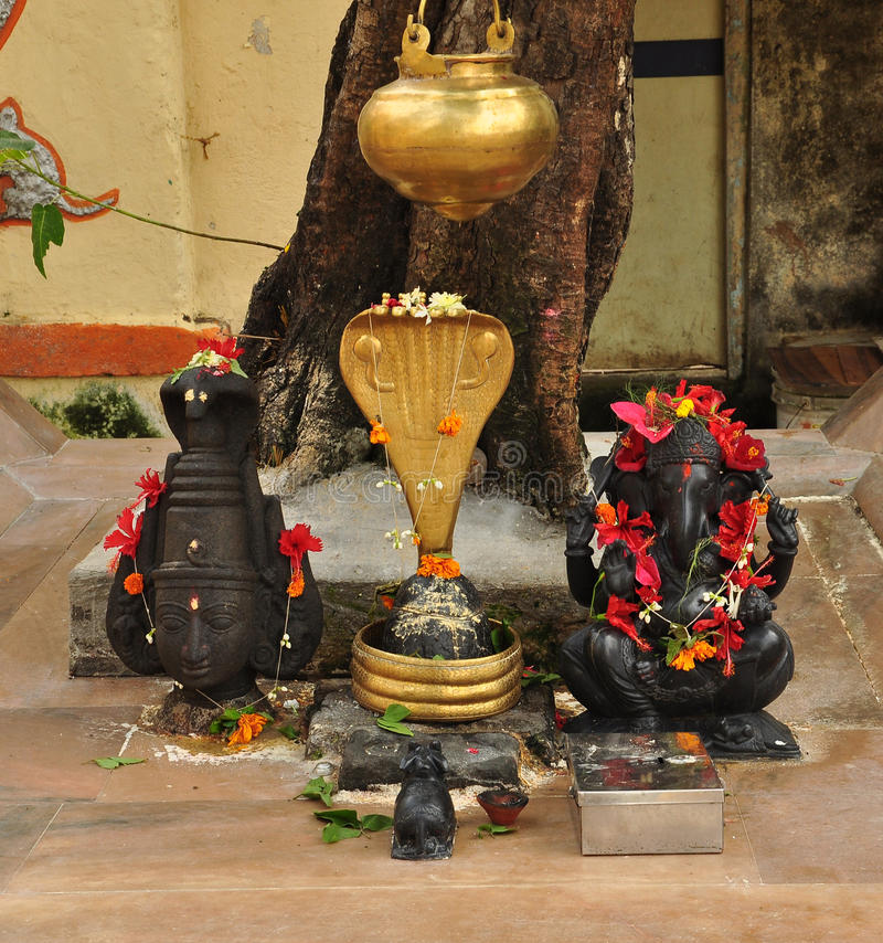 Ganesh and a devi statue. Small Indian worship shrine royalty free stock images