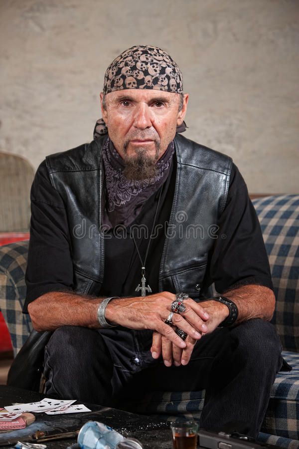 Gang Member Staring Ahead. Frowning gang member in leather vest in cold stare royalty free stock images