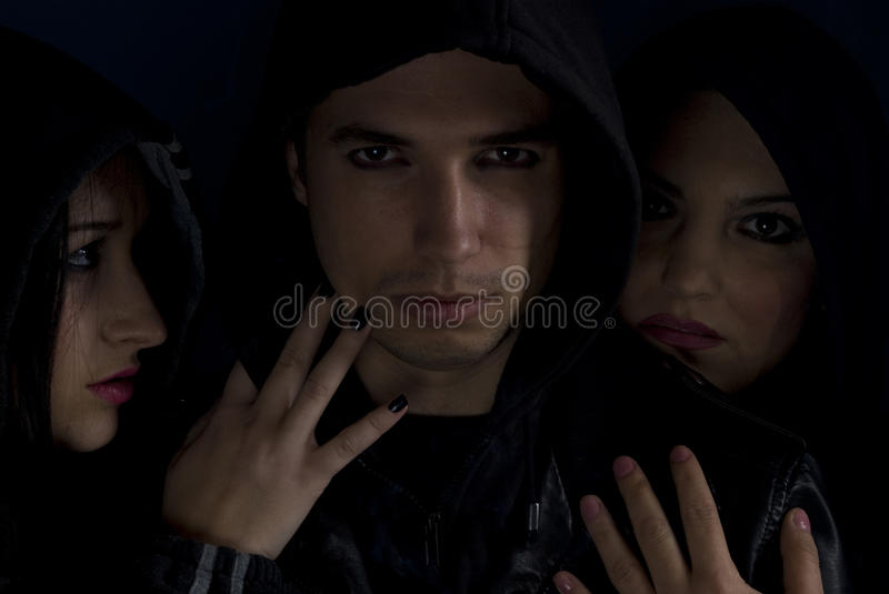 Gang members. Gang guy member in the middle of two passionate women with black hood ,concept of bad urban street boys,check also