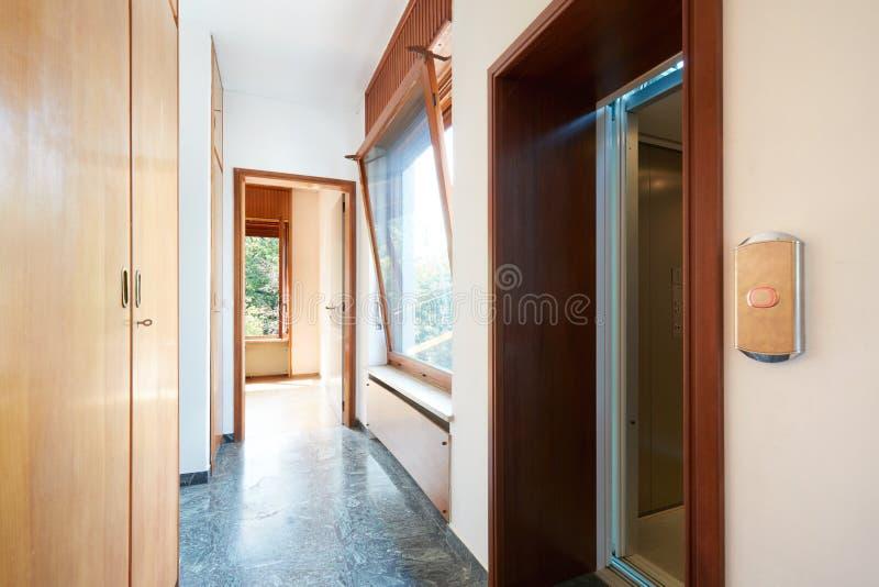 Gang met houten garderobe, venster en liftdeur in buitenhuis royalty-vrije stock afbeelding