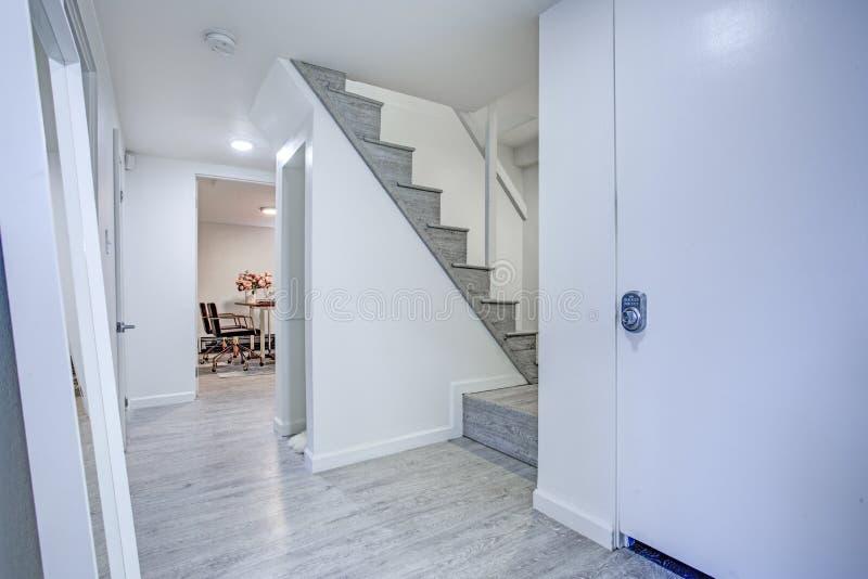Gang met zuivere witte muren en grijze hardhoutvloer stock afbeeldingen