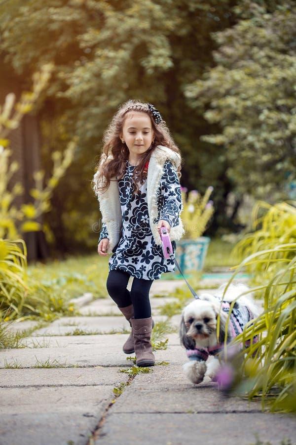Gang in park - leuk meisje die haar hond op leiband houden stock fotografie