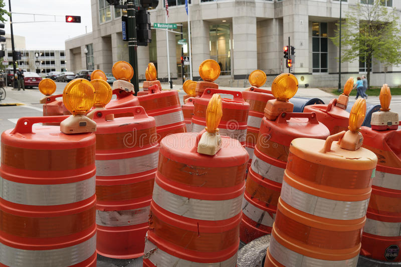 Gang of road construction barrels hanging around street corner. Road construction barrels by the side of the road or a a gang of construction barrels quietly royalty free stock photo
