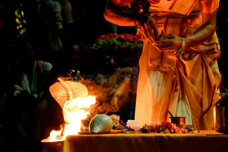 Close up of young hindu priest performing daily ritual ganga aarti ceremony with fire and symbolic snake. Ganga aarti ceremony with fire and symbolic snake stock images