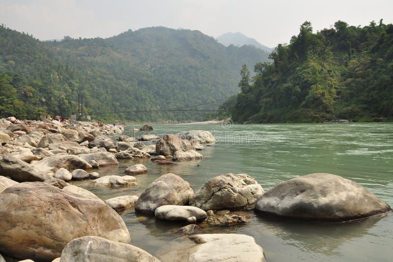 The Ganges, Indian sacred river near Rishikesh, India. The hindu sacred river Ganges among heavy forested hills near Rishikesh, India. Morning hazy summer light royalty free stock image