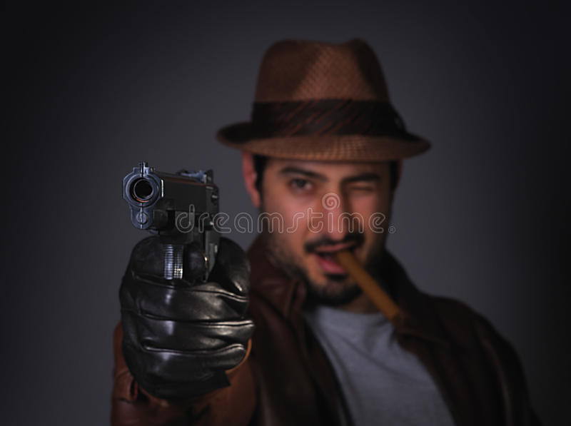 Gangster aiming gun at you. A badass gangster aiming his gun at you royalty free stock images