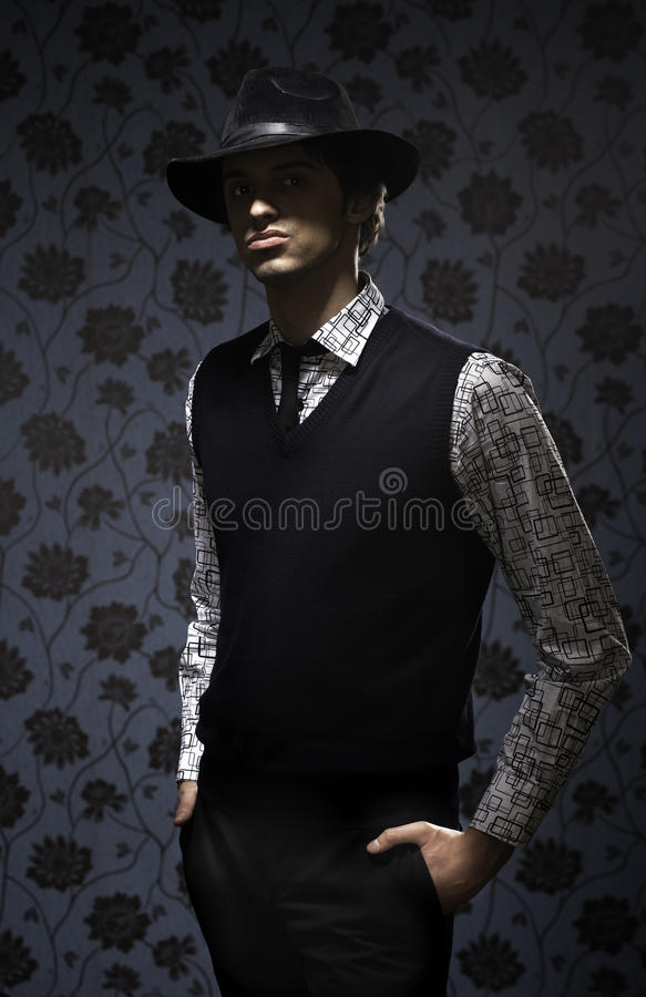Gangster in dark key on wallpapers background. Portrait of gangster in dark key on wallpapers background royalty free stock image