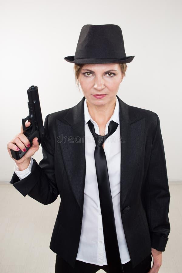 Gangster della ragazza che tiene una pistola Vestito e cappello classici fotografia stock