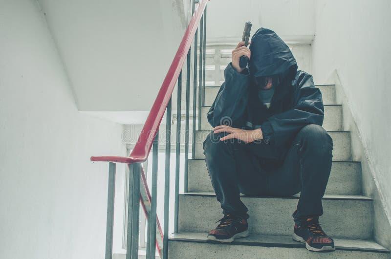 Gangster, der auf Treppe, allein mit seinen Gedanken und seinen Gewehren sitzt stockfotos