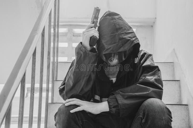 Gangster, der auf Treppe, allein mit seinen Gedanken und seinen Gewehren sitzt lizenzfreie stockfotos