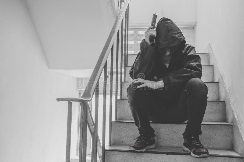 Gangster, der auf Treppe, allein mit seinen Gedanken und seinen Gewehren sitzt lizenzfreie stockfotografie