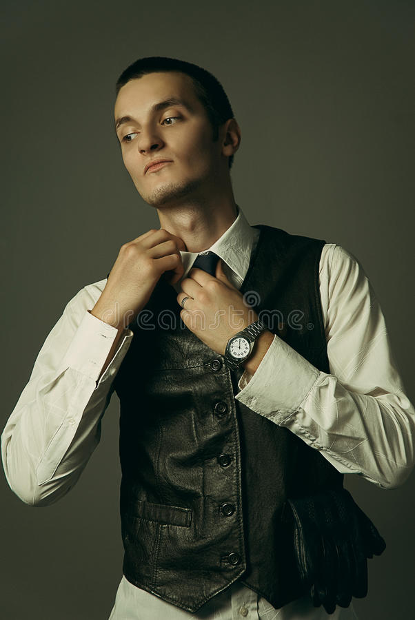 A gangster is getting dressed. An old style image of a gangster in a suit and tie royalty free stock image