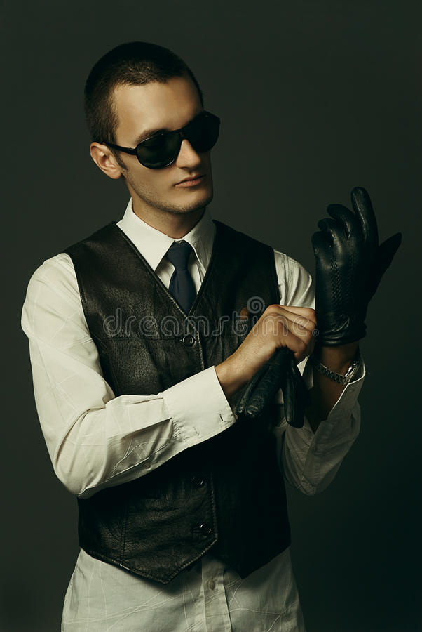 A gangster is getting dressed. An old style image of a gangster in a suit and tie stock photos