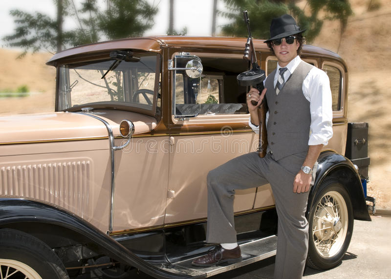Gangster holding a tommy gun. Young man dressed as a gangster, holding a Tommy gun in his right hand, standing next to a 1930 Model A vintage car with his foot royalty free stock images