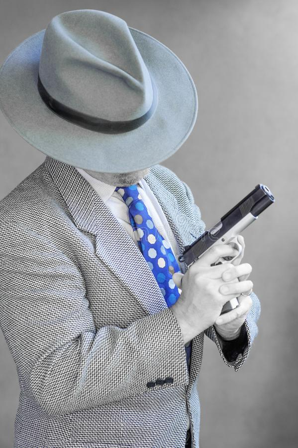 Gangster wears a fedora and hold a large gun royalty free stock photo