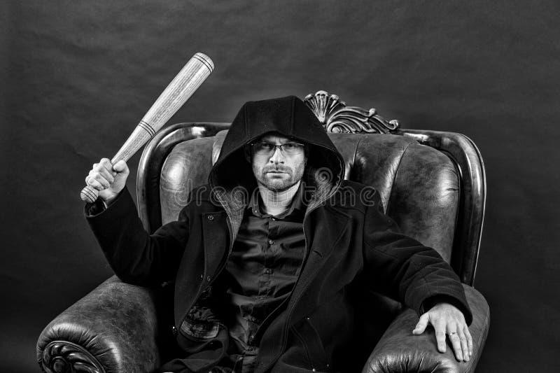 Gangstergrabbslag med slagträvapnet Den skäggiga mannen med baseballslagträet sitter i fåtölj Brottslig kläderhuv i lag Brott ell arkivbilder