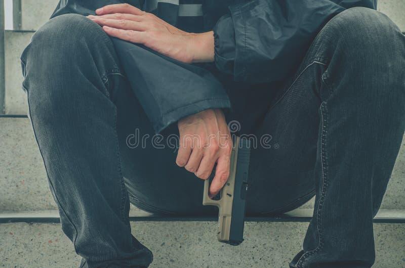 Gangstermänner, die ein Gewehr sitzt auf Treppe halten Ruhiges Sitzen der jungen Männer mit einem Gewehr auf ihm Hand allein stockfoto