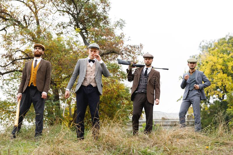 Gangsters stand with a dangerous weapon in their hands. Retro. Outdoors. royalty free stock image