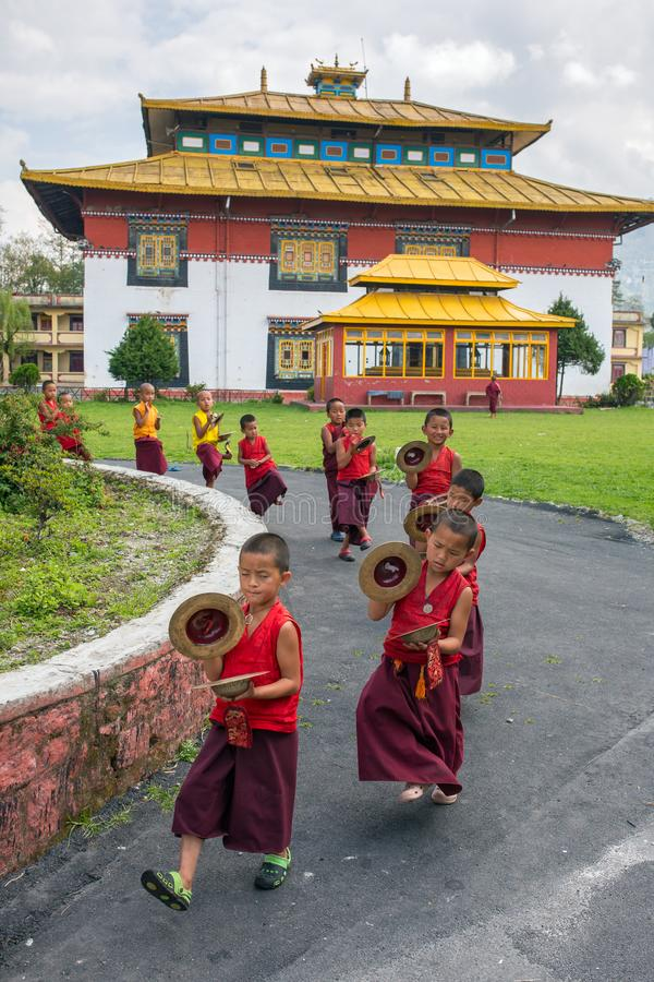Unidentified young novice buddhist monks in traditional red robes practicing in playing Tibetan music stock photos
