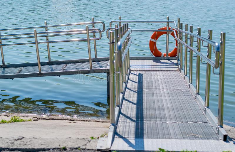 Gangway, descent from the shore to the water for the disabled. Rescue circle on the pier royalty free stock photography