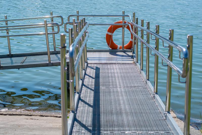 Gangway, descent from the shore to the water for the disabled. Rescue circle on the pier royalty free stock photo