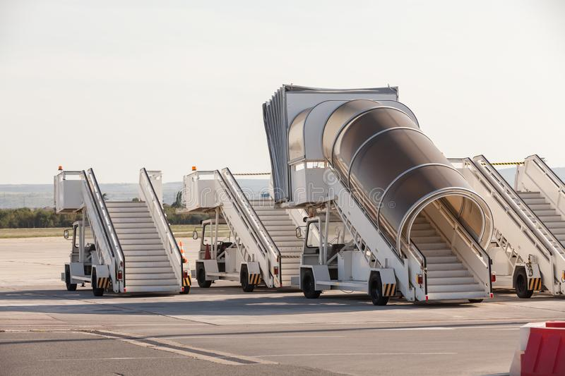 Gangways of airplan at the airport. Passenger`s boarding ramps. Passenger`s ladders. Traveling and waiting for flight at the. Airport stock photography