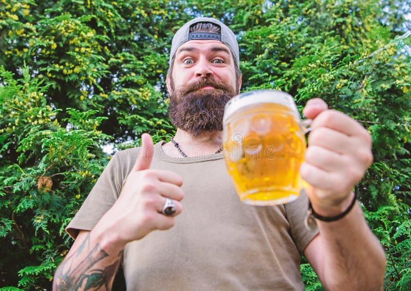 Ganha a melhor cerveja. O homem bebe segurando caneca de cerveja. O homem barbudo gosta de beber cerveja na natureza. hipster brut fotografia de stock