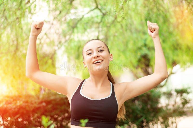 Ganhando, conceito do sucesso Bonita, a menina do esporte da aptidão exulta na vitória, levanta suas mãos acima imagens de stock royalty free