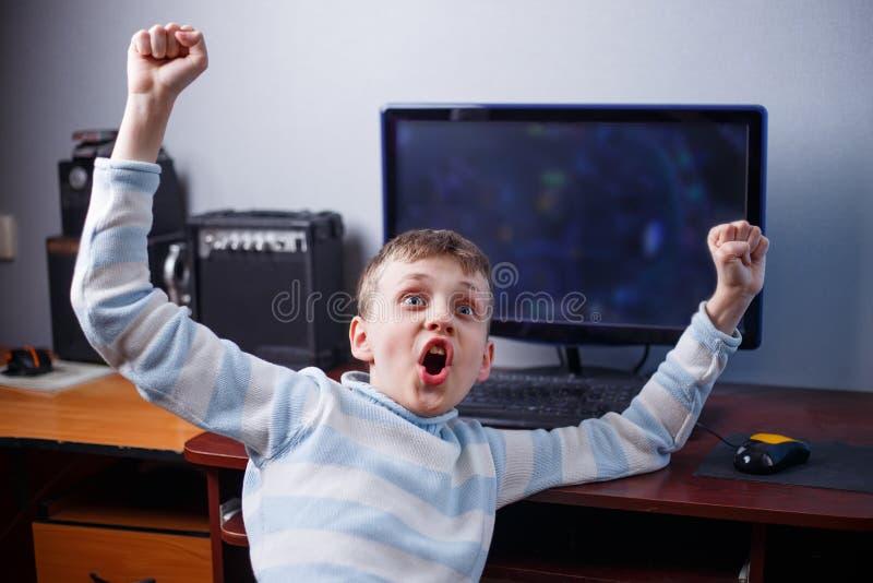 Ganhe o jogo Menino rejubilante feliz que joga o jogo de computador em seu ro fotografia de stock