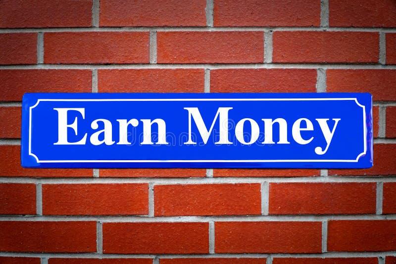 Ganhe o sinal de rua do dinheiro na parede de tijolo imagens de stock