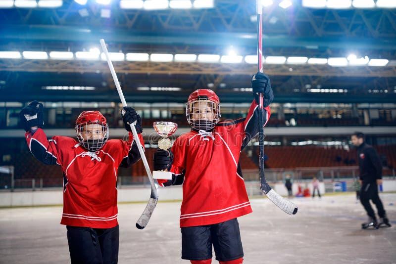 Ganhe o troféu na equipe dos jogadores dos meninos do hóquei do gelo fotos de stock