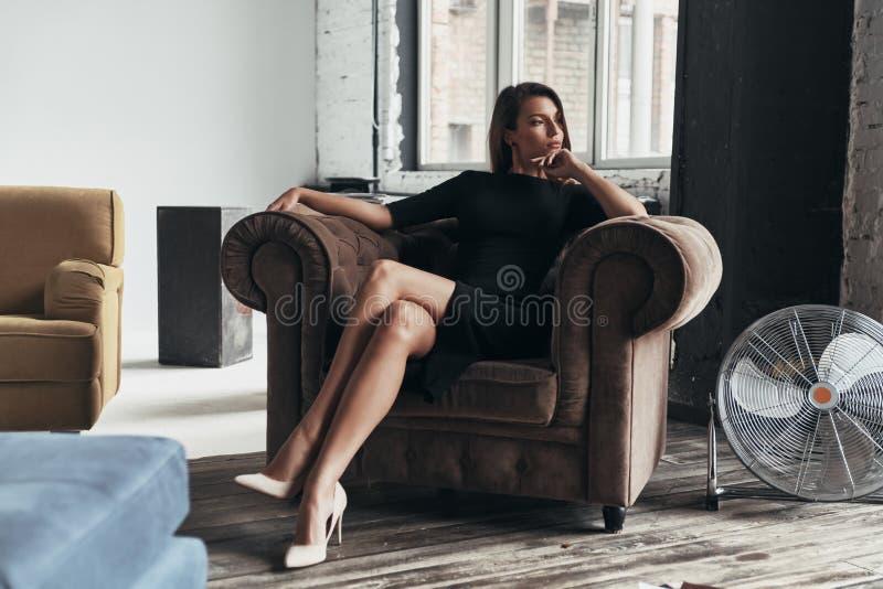 Ganska begrundande Attraktiv ung kvinna i elegant svart dre arkivbilder