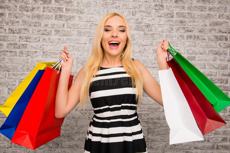 Ganska glad köpare som demonstrerar sina nya inköp royaltyfri fotografi