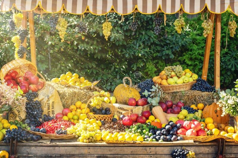 Ganska skärm för höstsäsongjordbruksmarknad Livliga frukter och grönsaker på den trägamla vagnen för höstgarnering - bild arkivbilder