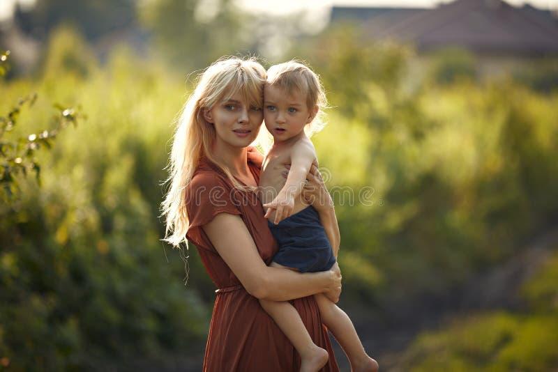 Ganska ung mor som bär med sig hennes älskade son royaltyfria bilder